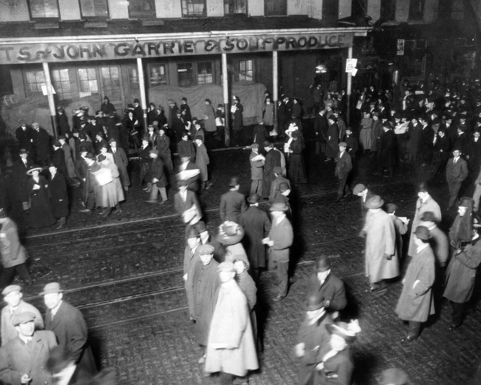 People gather in New York to await the arrival of survivors of the sinking of the RMS Titanic aboard the RMS Carpathia